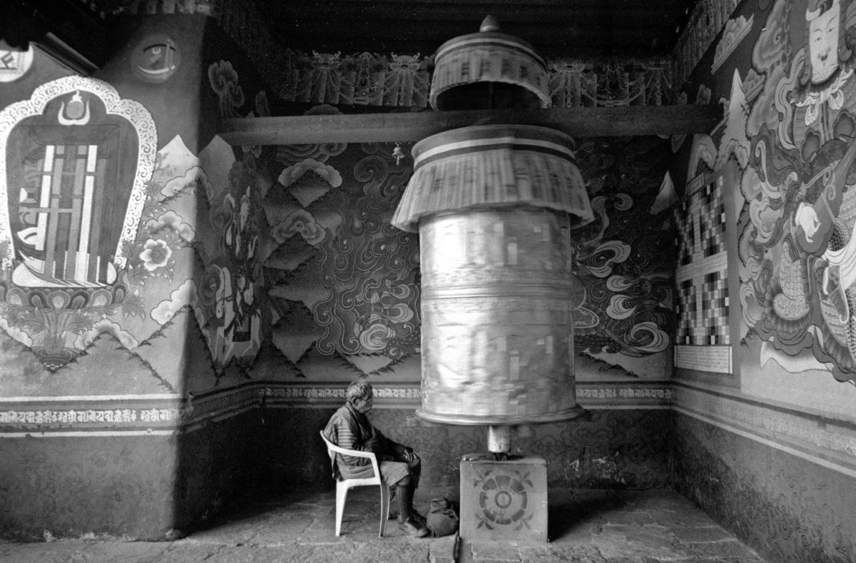 Monk in front of prayer wheel (Pic: Lester Ledesma)