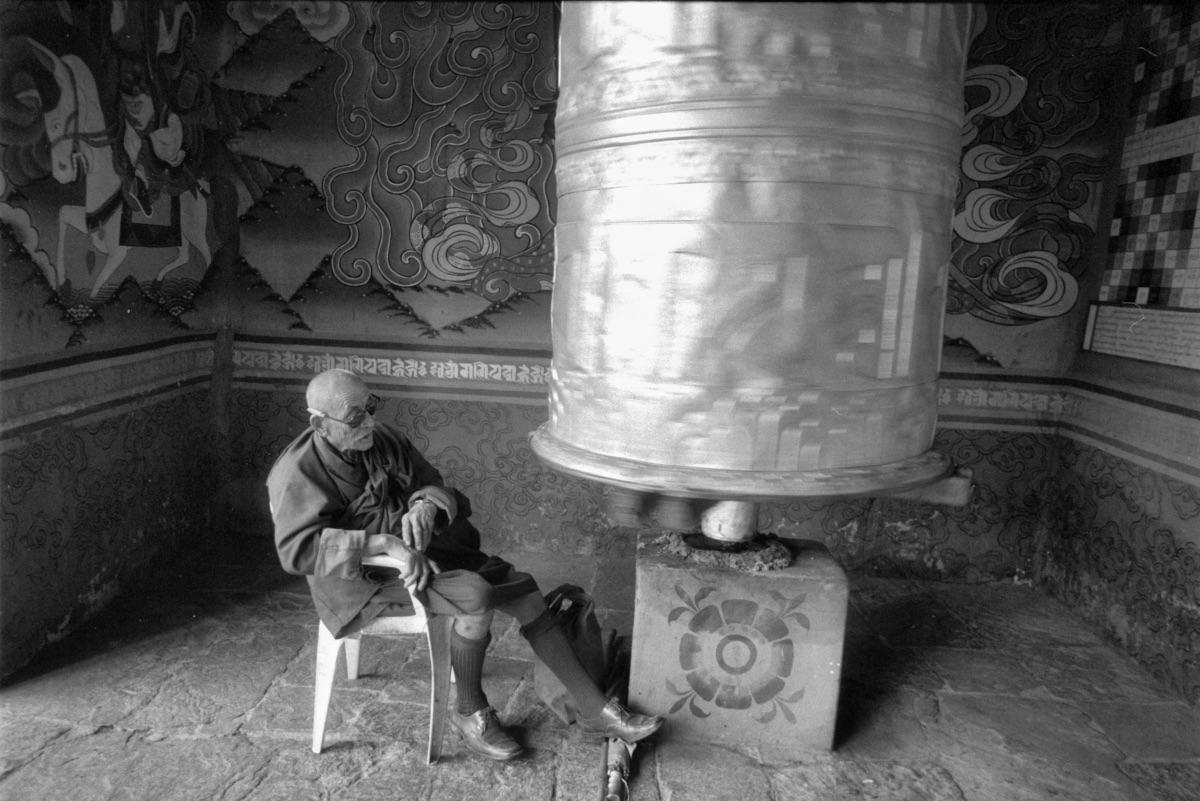 Monk by prayer wheel (Pic: Lester Ledesma)