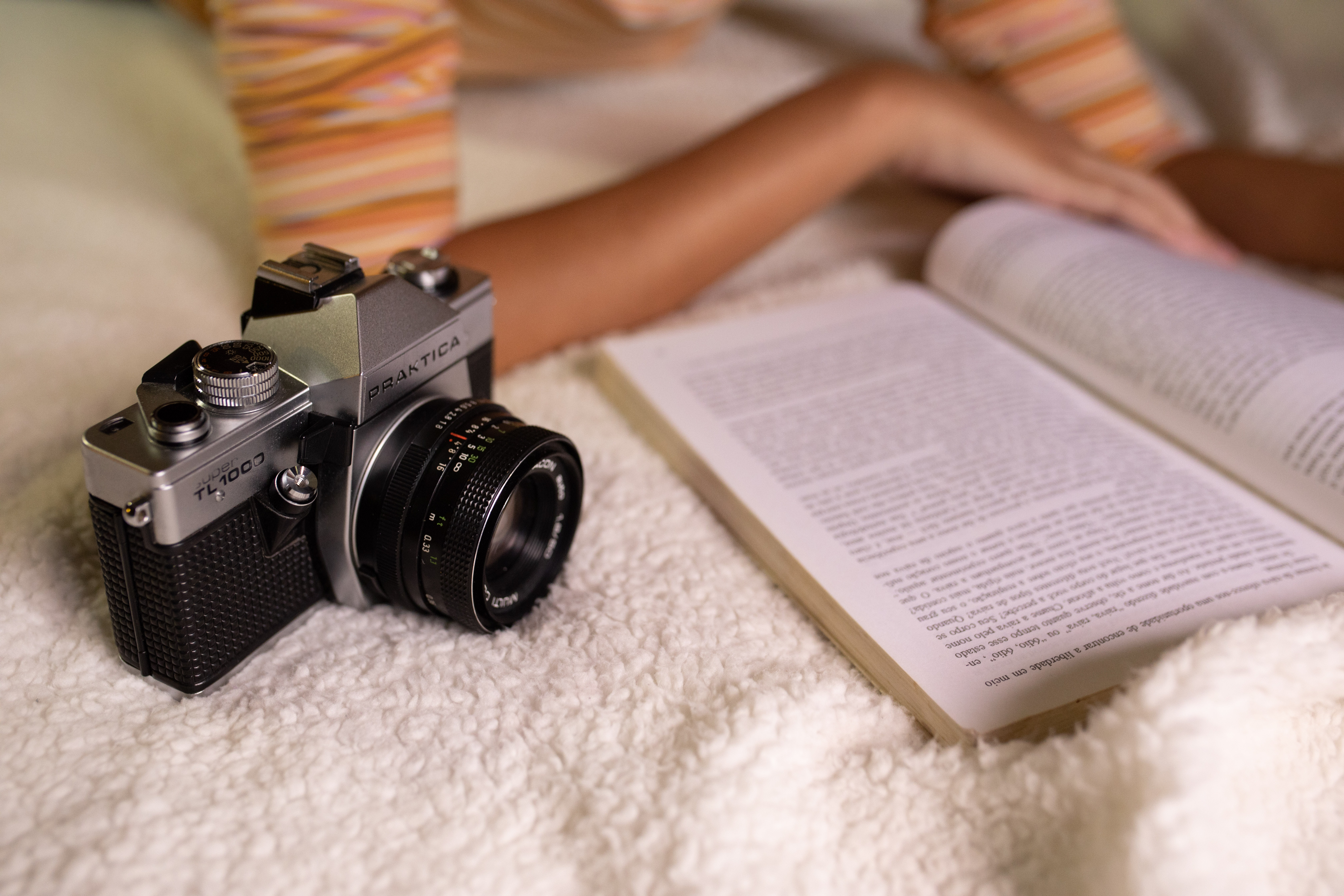 Woman reading book with film camera (Pic: Athena/Pexels)