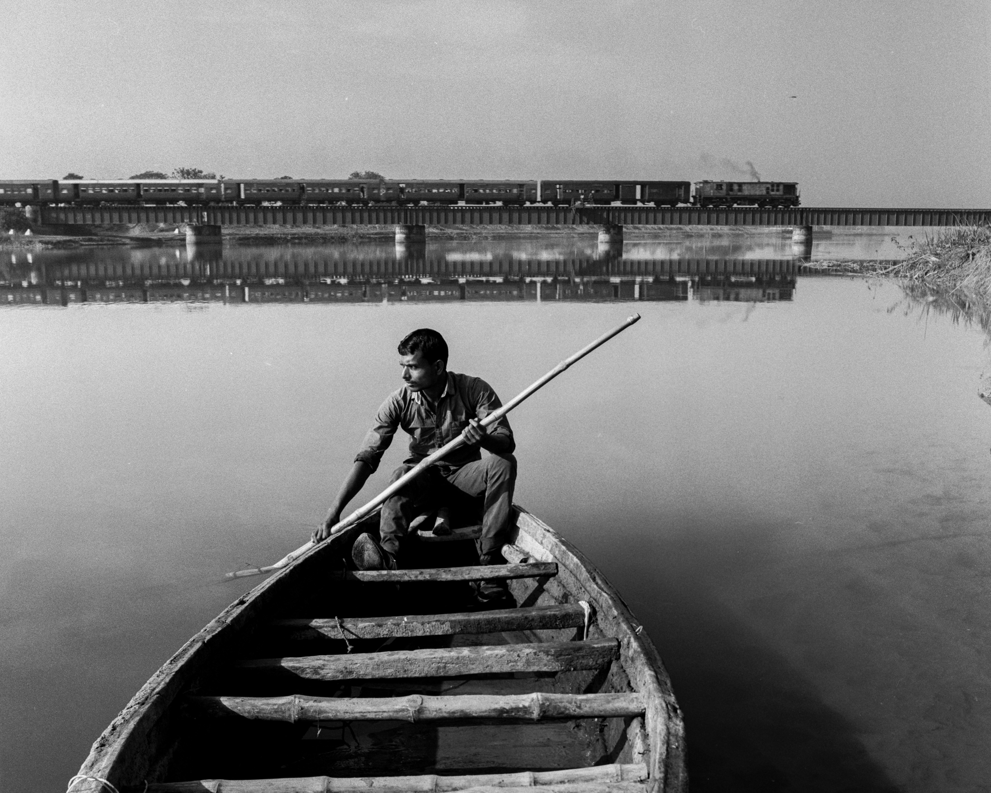 Man in boat with train behind (Pic: Nandakumar Narasimhan)